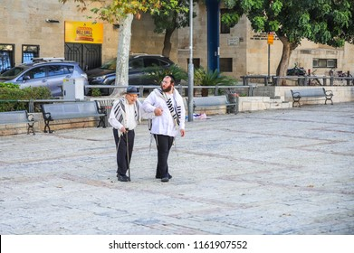 Jerusalem, Israel, August 18, 2018 : A young Jew leads an elderly Jew under the arm of an early morning for the morning prayer in the Jewish quarter in the old city of Jerusalem