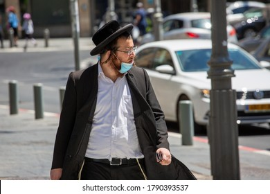 Jerusalem / Israel - August 2, 2020: Coronavirus Outbreak. Orthodox Jew wearing protective mask crosses a sunny street.