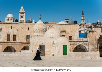 Jerusalem, Israel, August 20th, 2018: A Muslim woman wearing black hijab and walking at the square of the Golden Dome of the Rock, in an Islamic shrine located on the Temple Mount in the Old City