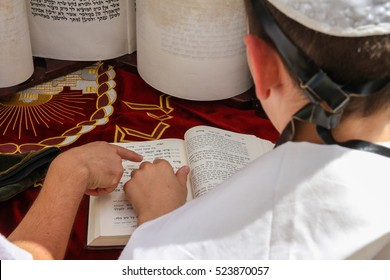 JERUSALEM, ISRAEL - AUGUST 25, 2016 : A young man finger pointing at a phrase in a bible book, while reading a pray at a Jewish ritual (Bar Mitzvah ceremony), in The Wailing Wall / western wall