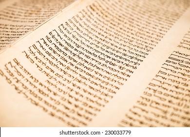 JERUSALEM, ISRAEL, CIRCA 2014. The Hebrew handwritten Torah, on a synagogue alter, illustrating Jewish holidays, during fests. Letters of scriptures close up.