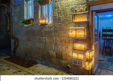 Jerusalem, Israel - December 09, 2018: Traditional Menorahs (Hanukkah Lamps) with olive oil candles, placed near the entrance, in the Jewish quarter, Jerusalem Old City, Israel