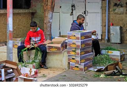 Jerusalem, Israel - December 1, 2017: man and adolescent are sorting out leek at Machane Yehuda Market in Jerusalem, Israel