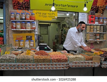 Jerusalem, Israel - December 1, 2017: man is selling dried fruits and nuts at Machane Yehuda Market in Jerusalem, Israel