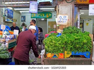 Jerusalem, Israel - December 1, 2017: man is selling vegetables and at Machane Yehuda Market in Jerusalem, Israel