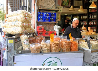 Jerusalem, Israel - December 1, 2017: man is selling dried fruits and nuts at Machane Yehuda Market in Jerusalem, Israel
