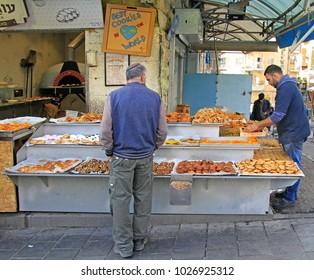 Jerusalem, Israel - December 1, 2017: man is selling pastries at Machane Yehuda Market in Jerusalem, Israel