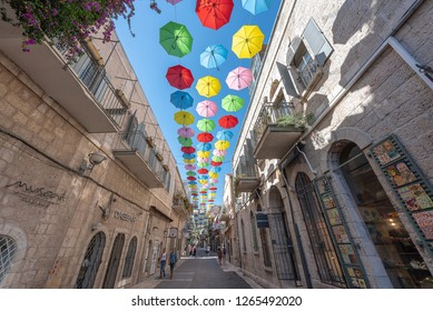 Jerusalem, Israel - December 15th, 2018: Yoel Moshe Solomon Street, decorated with colorful umbrellas, with locals and visitors, in the historic Nachalat Shiva district, Jerusalem, Israel