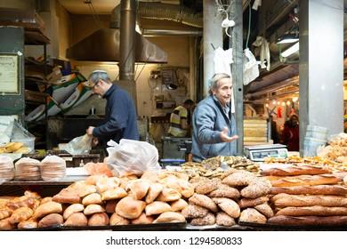 Jerusalem, Israel - December 24, 2018:A seniors bakers selling variety of hand made bread at old Jewish bakery  shop at Jerusalem market - Israel.
