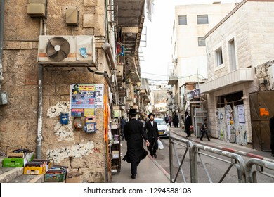 Jerusalem, Israel - December 24th, 2018: A street scene with two man in black, charity donation boxes on the wall in Ultra Orthodox Meah Shearim, Jerusalem district, populated by Haridi jews.