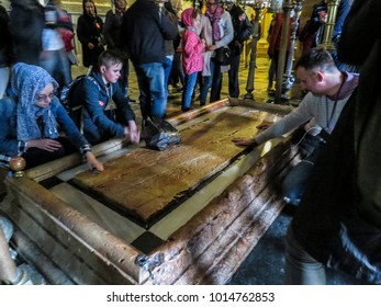 Jerusalem, Israel - December 28, 2017: Pilgrim prays at the Stone of Anointing or the Stone of Unction in the Church of the Holy Sepulchre in Jerusalem