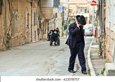 JERUSALEM, ISRAEL - DECEMBER 29, 2016: Orthodox Jewish man with mobile phone walk at street at jewish quarter in Jerusalem.