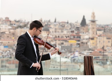 JERUSALEM, ISRAEL - FEBRUARY 10, 2013: Young jewish man playing the violin one a rooftops in Jerusalem.