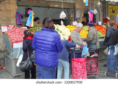 JERUSALEM, ISRAEL - February 14, 2019. Men and women with shopping trolleys are buying fruits and vegetables for shabbat at the Mahane (Machane) Yehuda market in the city center.