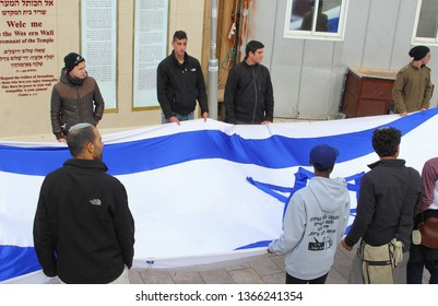 JERUSALEM, ISRAEL - February 14, 2019. Young Israeli men are holding the national flag of the State of Israel for a ceremony at the Western Wall.