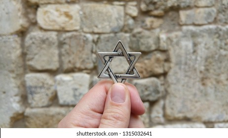 JERUSALEM, ISRAEL. February 15, 2019. Hand holding a David star Jewish star against the Small Kotel (Wailing Wall). Small Western wall, Jewish history and religion concept. Judaism, Temple Mount image