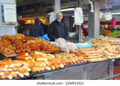 JERUSALEM, ISRAEL - February 15, 2019. Israeli man with kappah is selling different kinds of bread at the Mahane (Machane) Yehuda market.