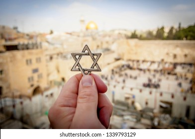 JERUSALEM, ISRAEL. February 15, 2019. Hand holding a Star of David, a Jewish religious symbol against the Western wall of the Jewish Temple in the Old city of Jerusalem. Judaism Zionism concept image.