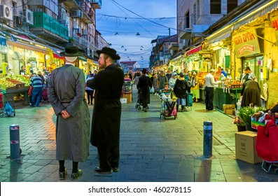 JERUSALEM, ISRAEL - FEBRUARY 18, 2016: Two friends-hasids, dressed in traditional elegant clothes, talking at the entrance of Mahane Yehuda market, on February 18 in Jerusalem.