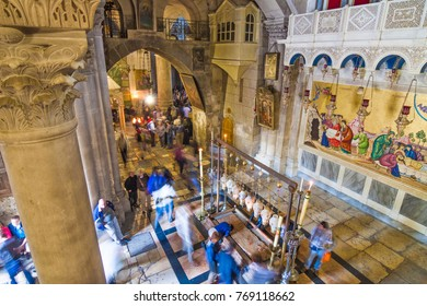 JERUSALEM, ISRAEL - FEBRUARY 25, 2011: Interior of Holy Sepulchre church with Stone of Anointing (of Unction) where Jesus' body have been anointed before burial and blurred moving figures of pilgrims