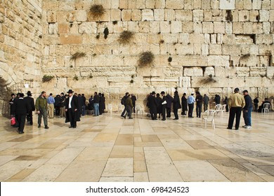JERUSALEM, ISRAEL - JANUARY 14, 2009: Men pray at the Western Wall. The Western Wall is a segment of an ancient wall that was built around 19 BCE by Herod the Great as part of the Second Jewish Temple