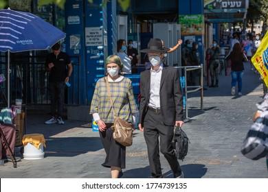 JERUSALEM, ISRAEL- JULE 12, 2020: Coronavirus Soars Among Ultra-Orthodox Jews. Religious Jewish couple wearing protective masks walk down the sunny street.