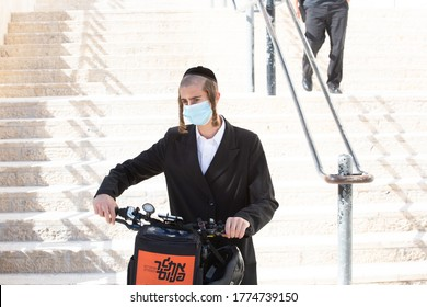 JERUSALEM, ISRAEL- JULE 12, 2020: Coronavirus Soars Among Ultra-Orthodox Jews. Religious Jewish young man wearing protective mask rides the scooter.