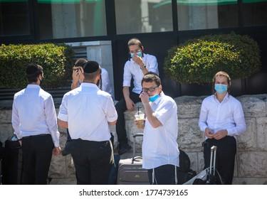 JERUSALEM, ISRAEL- JULE 12, 2020: Coronavirus Soars Among Ultra-Orthodox Jews. Religious Jewish people wearing face masks having a conversation.