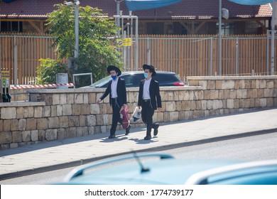 JERUSALEM, ISRAEL- JULE 12, 2020: Coronavirus Soars Among Ultra-Orthodox Jews. Religious Jewish people wearing protective masks walk down a sunny street.