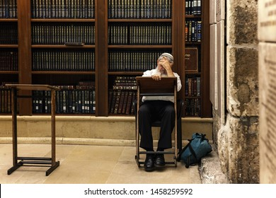 JERUSALEM, ISRAEL - JULY 04, 2016: Rabbi learns Torah sitting in front of wooden bookshelves with holy books in Cave Synagogue - old sacred place for Judaism, part of famous Western Wall in Jerusalem.