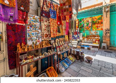JERUSALEM, ISRAEL - JULY 10, 2014: Stands with colorful oriental carpets, religious icons and gifts on bazaar - famous market place popular with tourists and pilgrims in Old City of Jerusalem.