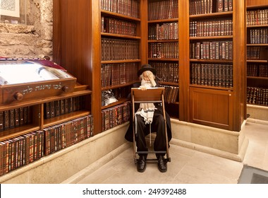 JERUSALEM, ISRAEL - JULY 10, 2014: Old rabbi learns Torah among wooden bookshelves with holy books in Cave Synagogue - old sacred place for Judaism which is part of famous Western Wall in Jerusalem.