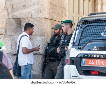 Jerusalem, Israel, July 14, 2017 : Soldiers guard the entrance to the old city of Jerusalem and talk with the local inhabitant in Jerusalem, Israel