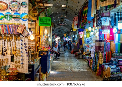JERUSALEM, ISRAEL - JULY 16, 2017: Narrow street among shops and stalls with traditional souvenirs at famous bazaar - market in Old City of Jerusalem, famous place with tourists.
