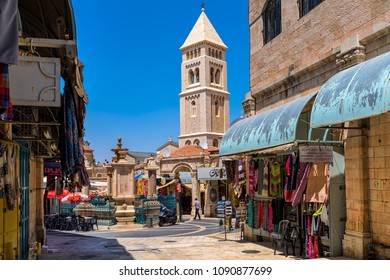 JERUSALEM, ISRAEL - JULY 16, 2017: Small square with fountain among gift shops as belfry on background in Muristan - famous historic complex of streets in Christian Quarter of Old City of Jerusalem.