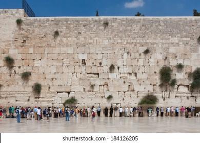 Jerusalem, Israel - July 18, 2010: People pray at the western wall, Jerusalem, Israel wide shot with blue sky.