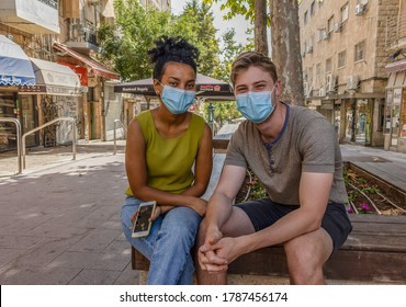Jerusalem, Israel - July 30th, 2020: A couple of young israelis wearing COVID masks on a nearly emty Jerusalem, Israel, street.