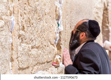 Jerusalem, Israel - June 14, 2018: Jewish people praying against the Western Wall, the second holiest place to the Jews. The Wall is the last remnant of the second temple of Jews in Jerusalem.