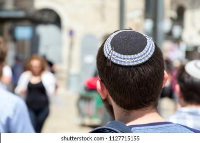 Jerusalem, Israel - June 14, 2018: Jewish man walking in the ancient streets of the old city of Jerusalem wearing a kippah or yarmulke, a traditional Jewish headwear.