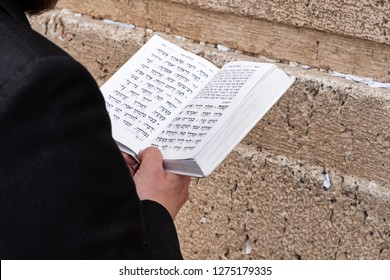 JERUSALEM, ISRAEL - JUNE 14, 2018: A man reading the torah and praying at the Wailing Wall in the Old City of Jerusalem in Israel.