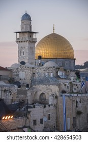 JERUSALEM, ISRAEL - JUNE 15, 2015: The minaret of a mosque and the Dome of the Rock, golden stand over the old city of Jerusalem , in the evening