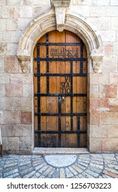 Jerusalem, Israel - June 15, 2018: Ancient streets and buildings in the old city of Jerusalem. Wooden door that indicates the place is the 6th sation of Via Dolorosa.