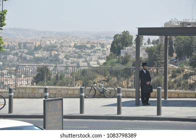 Jerusalem, Israel, June 16, 2010: Panoramic view of the houses on the hill of the city and the orthodox Jew in black waiting for the transport at the bus stop. Real people. Day of Jerusalem