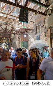 Jerusalem, Israel - June 16, 2018: Ancient streets and buildings in the old city of Jerusalem. Group of pilgrims touring Via Dolorosa.