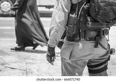 JERUSALEM, ISRAEL. June 20, 2017. Armed with an M-16 Israel border police officer  at the terror attack site by the Damascus gate of the Old city of Jerusalem. Security black and white stock image.