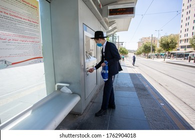 JERUSALEM, ISRAEL- JUNE 24, 2020: COVID-19 Post-lockdown Routine. Religious Jewish Orthodox wearing protective masks buys a tram ticket.
