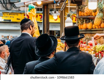 Jerusalem, Israel - Mar 16, 2018: Jewish ultra-orthodox people inspect pineapples at Jerusalem's Shruk Machane Yehuda market, which has over 250 food stalls offering local produce