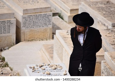 JERUSALEM, ISRAEL - March 11, 2018: Orthodox Jewish man walking through the Jewish cemetery and visiting his deceased.