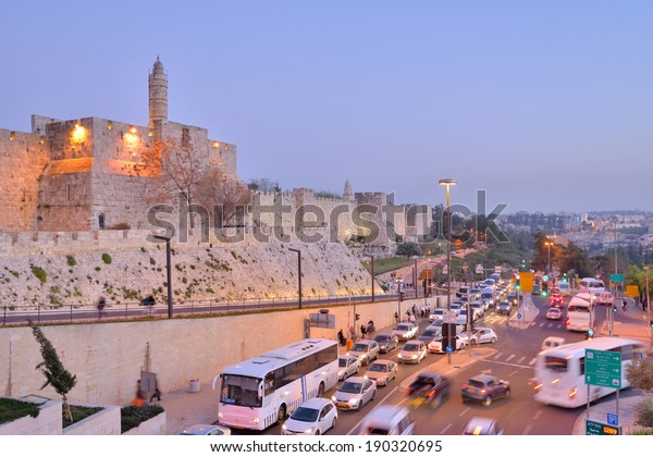 JERUSALEM, ISRAEL - MARCH 20, 2014: Car traffic under the walls of the Old City listed as UNESCO World Heritage site since 1981. Walls were built in 1538, under Suleiman the Magnificent