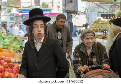 JERUSALEM, ISRAEL - MARCH 31, 2017: Undefined orthodox jewish boy and elderly woman at Mahane Yehuda Market, popular marketplace in Jerusalem, Israel